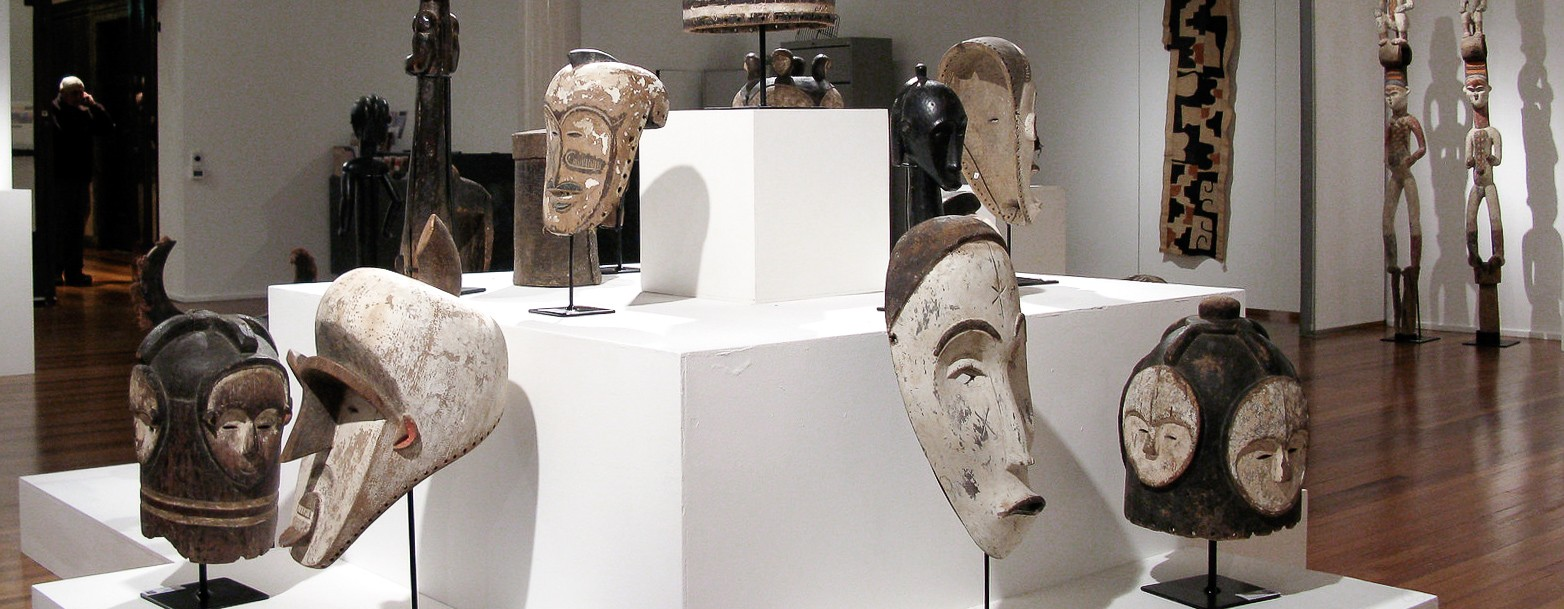 Masks from Gabon: African Ngil masks and Ngontang helm masks presented in a traditional African art gallery